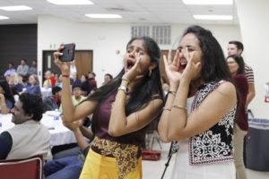 Abhilash Kolla, computer science senior, and Sindhu Thandra,computer science graduate student, yell and cheer on their friends during the traditional Diwali celebration, sat, Nov. 6, 2017, at the Sikes Lake Center. Photo by Sara Keeling