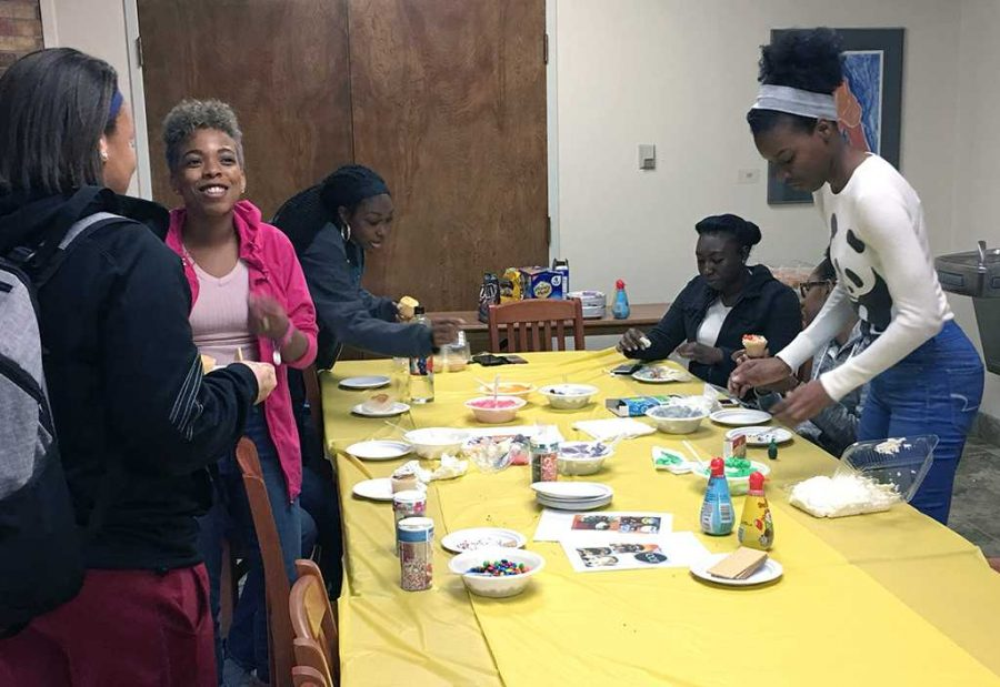 Angelica Symonette (right) helps students decorate their cupcakes Oct. 31. Symonette brought in candies such as M&Ms and sprinkes along with frosting for the UPB event. Photo by Latoya Fondren