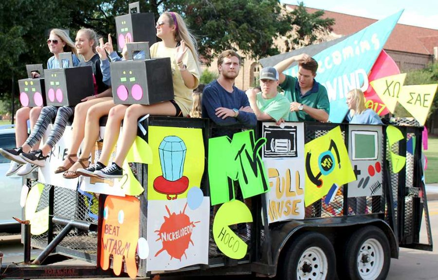 Chi Omega and Sigma Alpha Epsilon members rock to music with their boom box heads riding on their neon covered float for the Homecoming Parade.