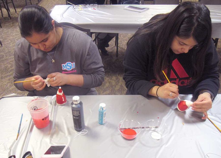 Leslie Picasio, athletic trainer freshman, and Marisa Gomez, radiology junior, are painting their santa ornaments during the holiday decorating class in the Clark Student Center, Kiowa Room on Dec. 5. Photo by Latoya Fondren