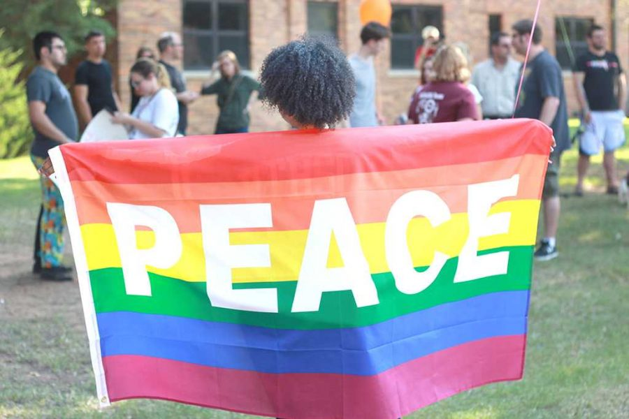 Shaniece Dutch, sociology senior, holds up a pride flag with the word peace on it during the Resist Hate Rally held at the Sunwatcher Plaza on Sept. 1. Photo by Justin Marquart