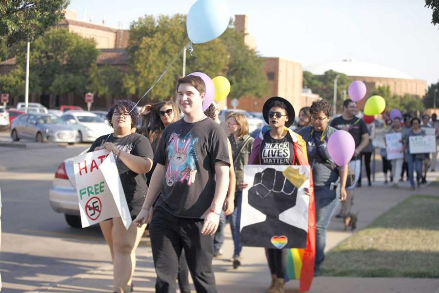 Zarya Maitao, mass communication sophomore, Jessie Tidwell, education sophomore and Zaquera Wallace, biology junior, flashes color and march in the Resist Hate Rally held in Sunwatcher Plaza on Sept. 1.