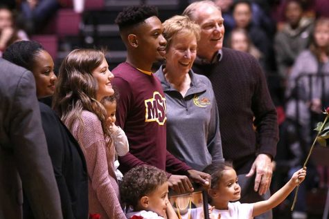 Devante Pullum, criminal justice senior, poses with coaches and family members during the honoring of seniors in between basketball games in D.L. Ligon Coliseum on Feb. 10. Photo by Rachel Johnson
