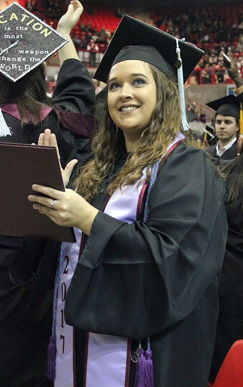Alyvia Nichols, interdisciplinary studies, claps and looks to her people who are in the audience for her during the end part of commencement where the graduates shout-out and clap to the members in the audience who were there for them through their college experiences. Photo by Rachel Johnson