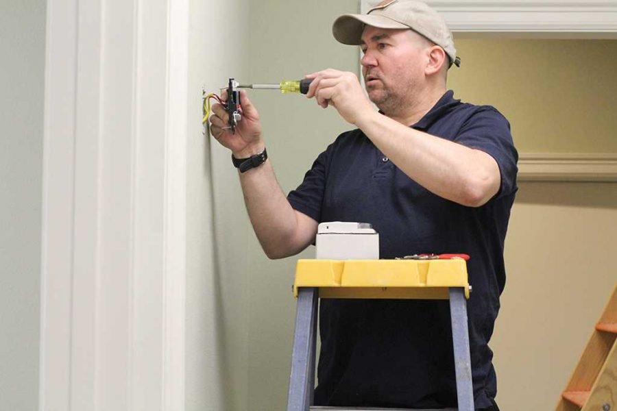 Joel Murrary installs a fire alarm in the new housing building in Feb. 19. Photo by Cortney Wood