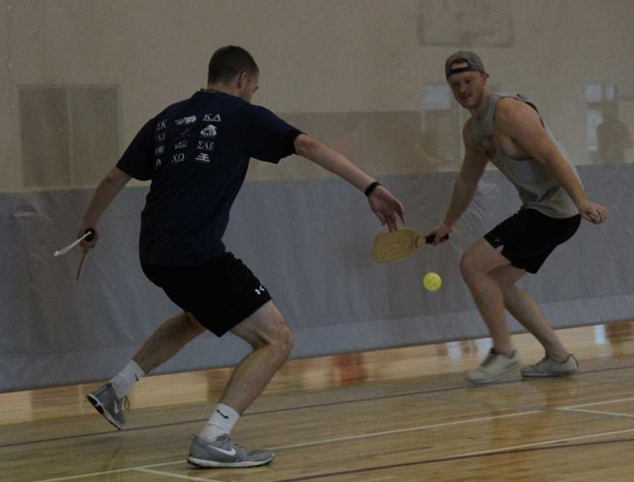 To save their first successful rally at the intramural Pickleball tournament, Mike Richardson, Redwine Student Wellness Center assistant director, and Patrick Moor, sports and leisure senior, rush to bat back the ball on Friday, Feb. 16, 2018 at the Redwine Wellness Center. Photo by Cortney Wood.