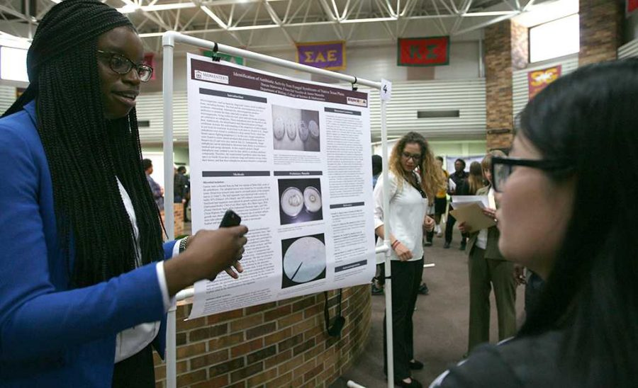 Dorcas Matuwana, biology senior, presents with partner Chiara Del Vecchio, chemistry junior, on identification of antibiotic activity during EUREKA on April 27, 2017. Photo by Arianna Davis