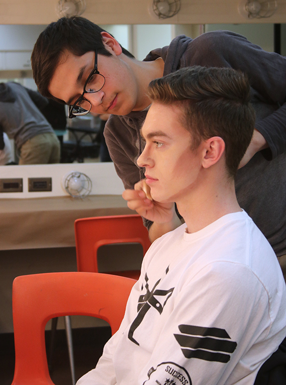 As a way to teach Samuel Mitchell, mass communication sophomore, how to correctly apply his makeup, Christopher Cruz, theater junior, demonstrates how to do it for the first time on Friday, Feb.16, 2018. Photo by Joanne Ortega
