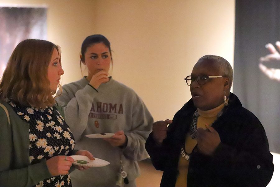 Siany Kloss, art freshman, and Alex Blake, finance senior, talk to artist Victoria Meek during open recitption in the Juanita Harvey Art Gallery on April 6. Photo by Justin Marquart