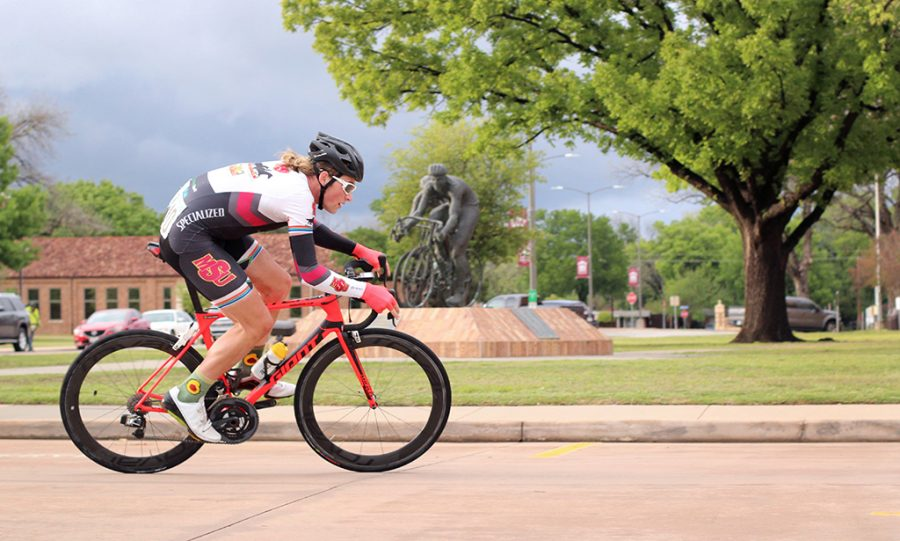 Joshua Buschel, accounting and finance junior, rounds the corner of Council Dr. and Comanche Trail in front of the Hotter N' Hell 100 statue infront of the Hardin Building at the 2018 Vuelta del Viento at Midwestern State University, Saturday April 21, 2018. Photo by Rachel Johnson