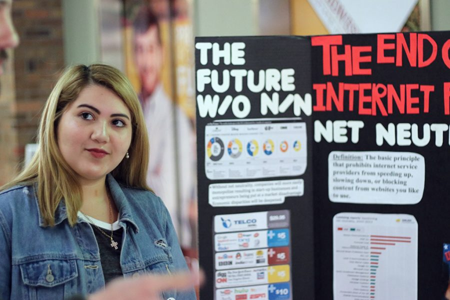 Elizabeth Chavarria, management junior, gets people to sign a petition to get Stephen Santellana, mayor of Wichita Falls, to support net neutrality at the net neutrality booth in the Dillard Lobby on the first floor on April 9, 2018. Photo by Justin Marquart