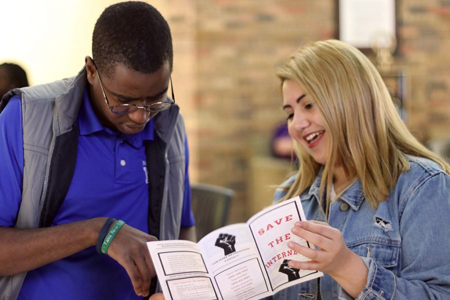 Elizabeth Chavarria, management junior, shows Kuda Bepswa, management senior, a flier about saving net neutrality at the net neutrality booth in the Dillard Lobby on the first floor on April 9, 2018. Photo by Justin Marquart