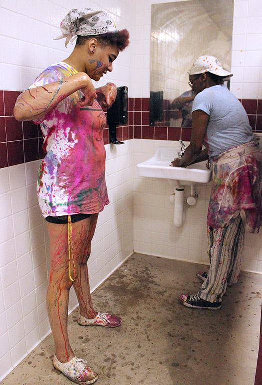 Zaquera Wallace, biology junior, waits for Adrienne Hill, sociology sophomore, to be done using the sink so she can rinse some of the paint that began to stick on her legs off, Friday April 6, 2018. Photo by Rachel Johnson