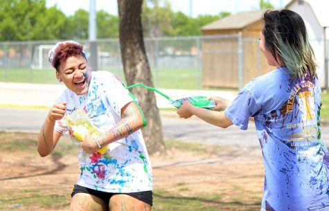 Amy Levy, biology sophomore, squirts her yellow team rival Zaquera Wallace, biology junior, with green paint during the Paint Fight held behind the Wellness Center, Friday April 6, 2018. Photo by Rachel Johnson