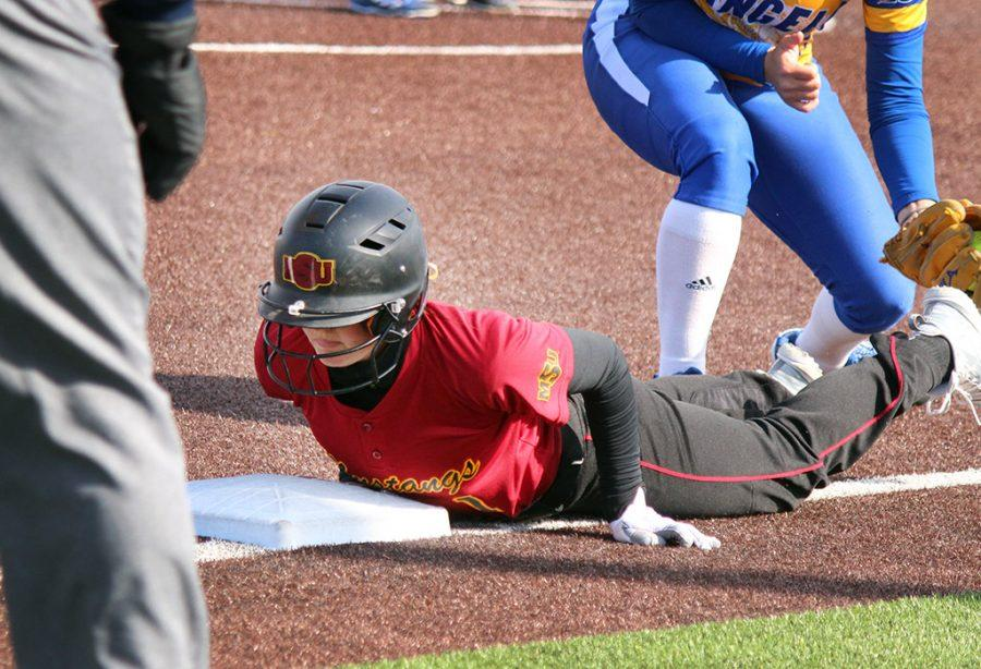 Caycee Griffin, biology freshman, slides back to third and is safe, after the opposing team catches her teammates fly ball, Saturday April 7, 2018. Photo by Rachel Johnson