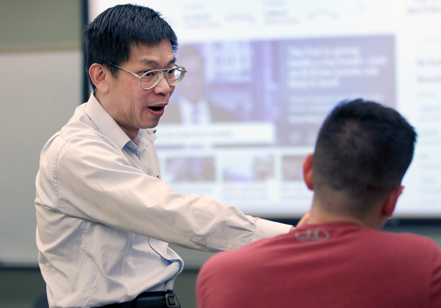 Adam Lei, Bridwell distinguished professor of finance, answers Eric Gamboa, finance junior, question about bonds before class at Dillard on Wednesday, April 18, 2018. Photo by Francisco Martinez