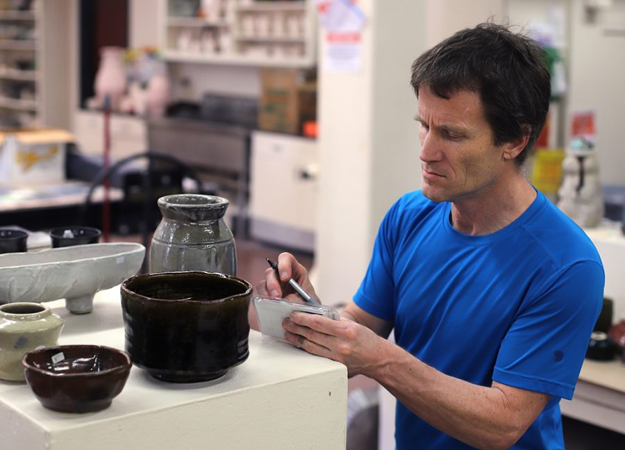 Steve Hilton, associate professor, puts price tags on ceramic pieces at the ceramic Mother's Day sale in the ceramics studio Fain C119 on May 10, 2018. Photo by Justin Marquart