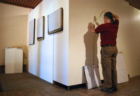 "Gary Goldberg, art professor and gallery director, adjusts the placement of art pieces for the senior exhibition Thursday, May 2, 2018. Goldberg said that since there were so many graduating art students this semester, the artwork had to be displayed in the foyer, as well as the actual gallery. ""We had to be more flexible this semester, but this space is mostly used as a path,"" Goldberg said. ""Our students often create pieces that challenge viewers emotionally and intellectually, so we have to create the galleries in a way that allows the viewer to make a choice if they want to engage in the art."" Photo by Brendan Wynne"