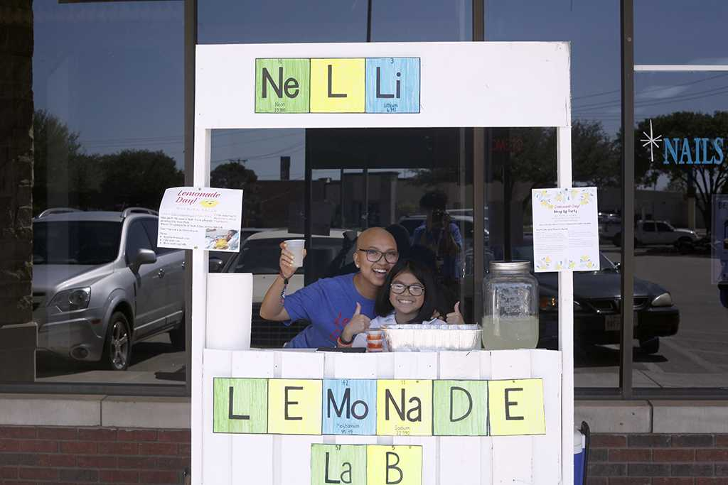 Entrepreneurs+Nini+Ho+and+her+younger+sister+Nelli+Ho+pose+behind+their+lemonade+stand+on+Saturday%2C+May+5%2C+2016.+%22My+dad+built+this+stand+and+worked+on+it+at+his+workshop+for+two+days+just+for+my+little+sister.%22+Ho+said.+Photo+by+Latoya+Fondren