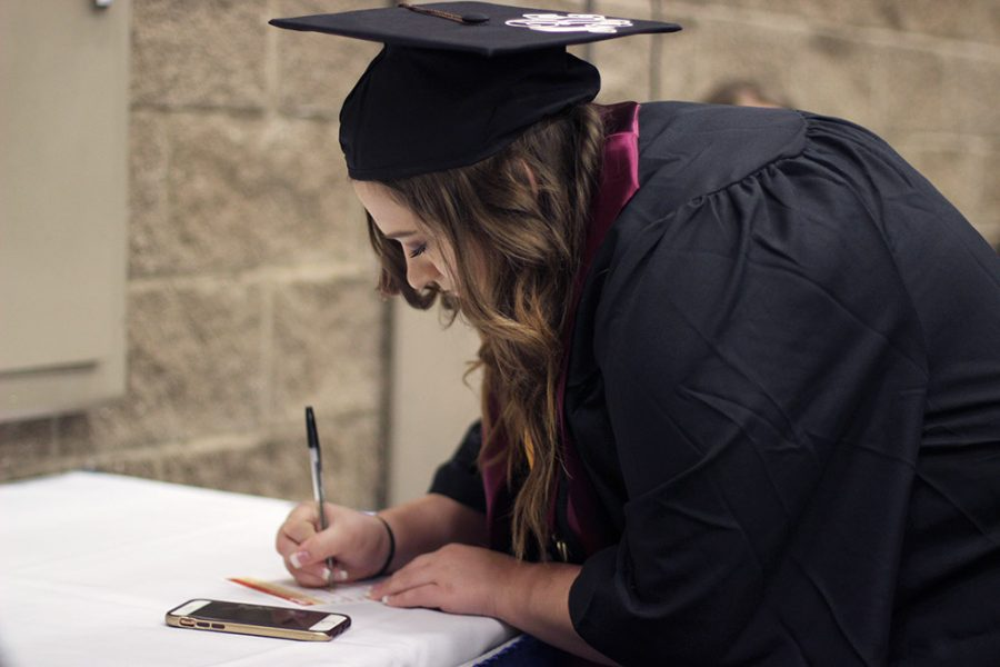 Morgan Barnes, business management, fills out her card for Commencement in the Multi-Purpose Events Center, Saturday May 12, 2018.
