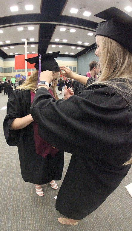 Allison Cooper, dental hygiene, helps Haley Buffington, dental hygiene, fix her cap while waiting for Commencement to being, May 12, 2018. Photo by Rachel Johnson