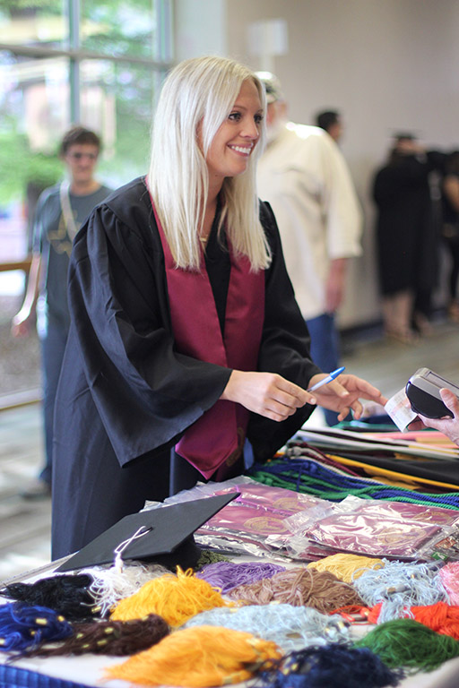 aTatum Crawford, bachelor of applied arts and sciences, purchases her tassel and graduation stoll before commencement in the Mutli-Purpose Event Center.
