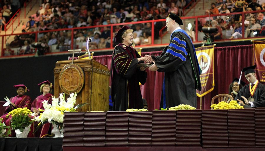 David Carlston, psychology professor, is presented a plaque by University Suzanne Shipley for winning the Hardin professor award for this year at Commencement, May 12, 2018. Photo by Rachel Johnson