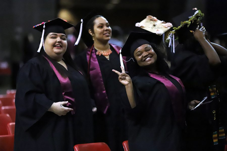 Yolanda Torres, humanities graduate, and Shaniece Dutch, sociology graduate, stand at their seats before the start of graduation at the spring 2018 graduation at Kay Yeager Coliseum on May 12, 2018. Photo by Justin Marquart