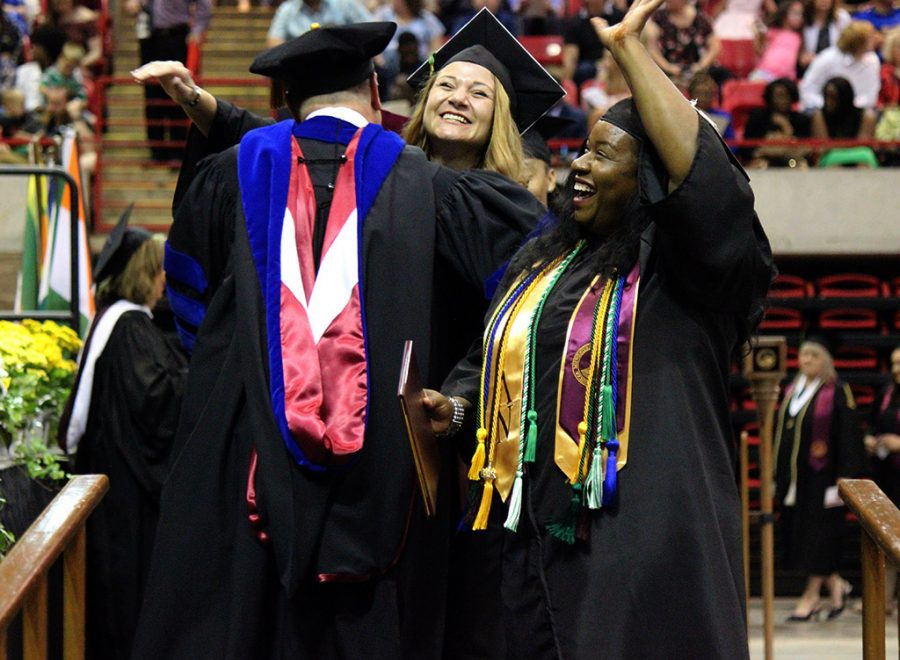 Tochia Anikwe, bachelor of science, waves to her family and friends in the audience after walking the stage at Commencement, May 12, 2018. Photo by Rachel Johnson