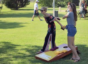 Courtney Lawerence, finance junior, and Brenna Rhodes, business managment junior, play bean bag toss during the president's picnic at Sikes House on Aug. 27. Photo by Stephen Gomez