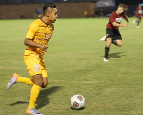 Erwin Regules, undecided junior and midfielder, dribbles the ball during the preseason game against Southern Nazarene at Stang Park on Aug. 22. Photo by Justin Marquart