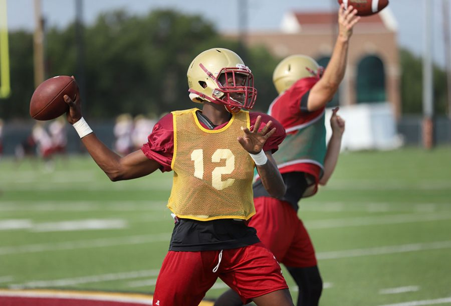 Prince Mavula, quarterback, runs drills during practice on the practice field on Aug. 22. Photo by Justin Marquart