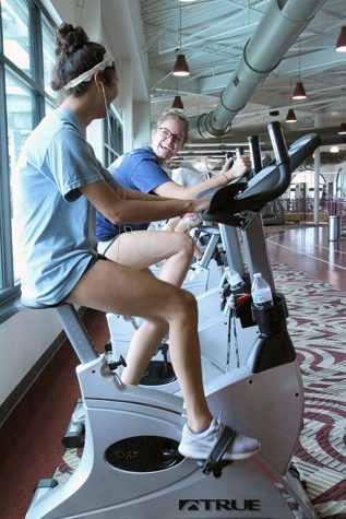 Acountability partners Michaela Disher and Allison Cisheros, radiology juniors, laugh at each other as they continue to push through on the cycling machines in the Wellness Center on Tuesday, Sept. 4, 2018. Photo by Cortney Wood