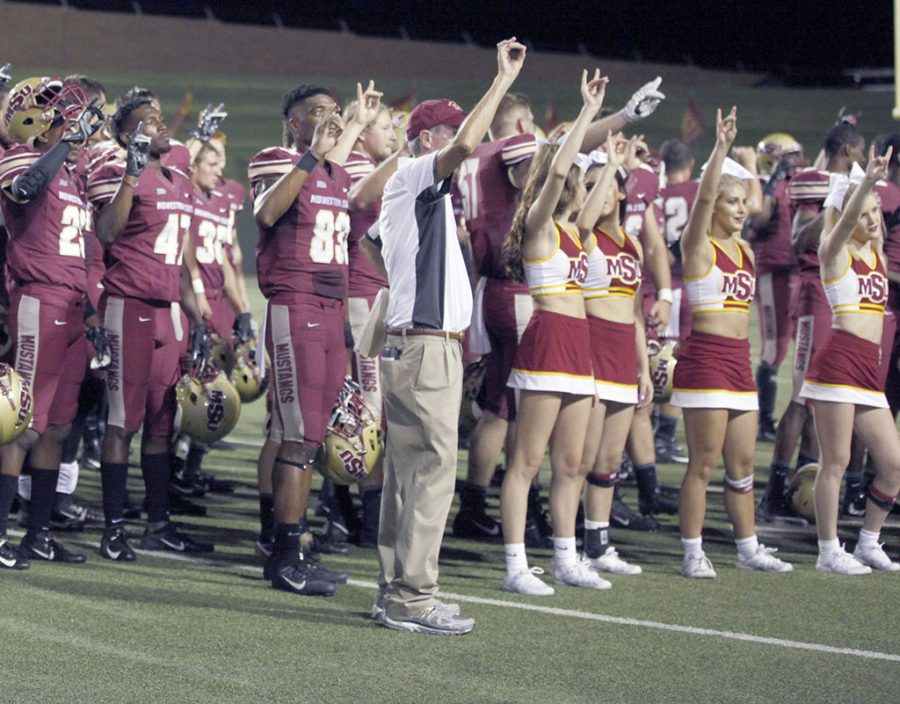 The football players and cheerleaders along side Bill Maskill hold up the mustang sign during the Almer Mater at the football game against Humboldt at Memorial Stadium on Sept. 1. Photo by Britnni Vilandre