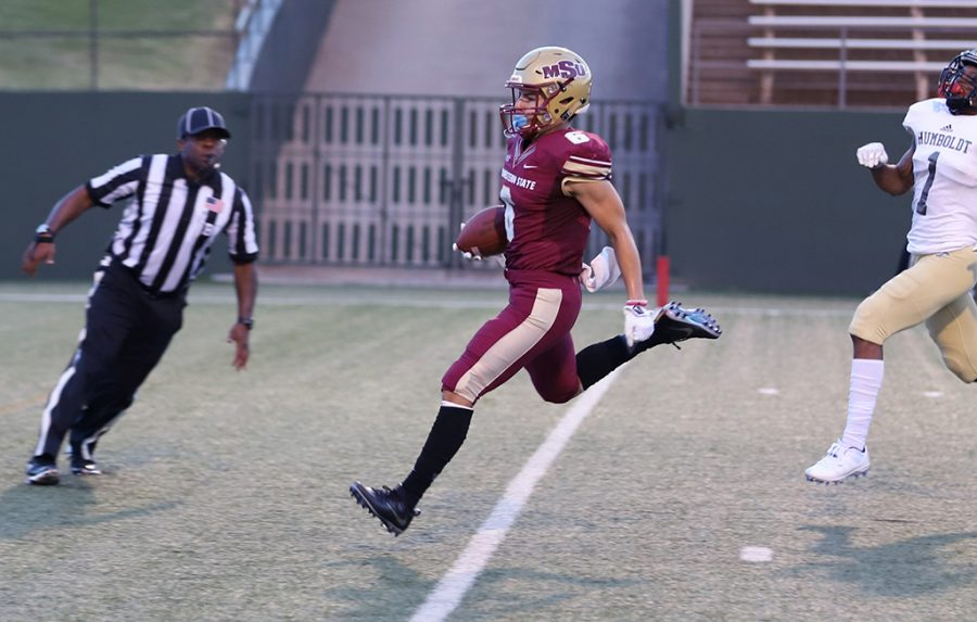 Bryce Martinez, criminal justice sophomore and wide reciever, scores a touchdown at the first football game against Humboldt at Memorial Stadium on Sept. 1. Martinez scored two touchdowns during the game. Mustangs win by 43 points, 55-12. Photo by Justin Marquart