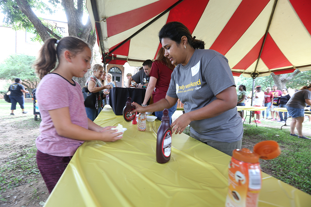 Dittika Gupta, assistant professor of curriculum and learning, with other faculty from the West College of Education serves ice cream at Family Day Oct. 6, 2018. Photo by Bradley Wilson