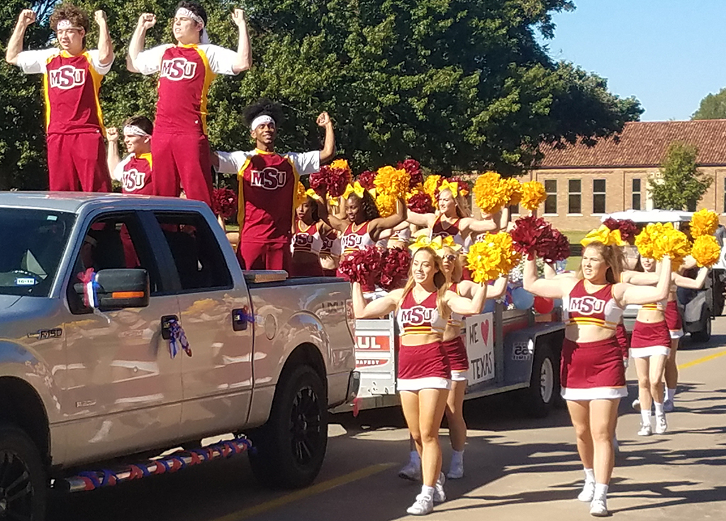 Cheer+leads+the+floats+in+the+Homecoming+Parade+on+October+27%2C+2018.+Phone+Photo+by+Stephen+Gomez