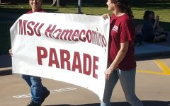 Taylor McCreary management senior and Jose Zambrano Graphic Design sophomore hold the Homecoming Parade banner on October 27, 2018. Phone Photo by Stephen Gomez