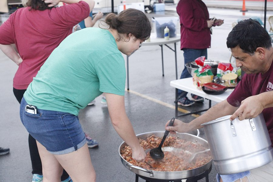 Lydia Acuña, freshman exercise physiology major, helps her dad, Poló, make discada for the Baptist Student Ministry booth at the tailgate on Oct. 6 2018 at Memorial StadiumPhoto by Jared Bruner