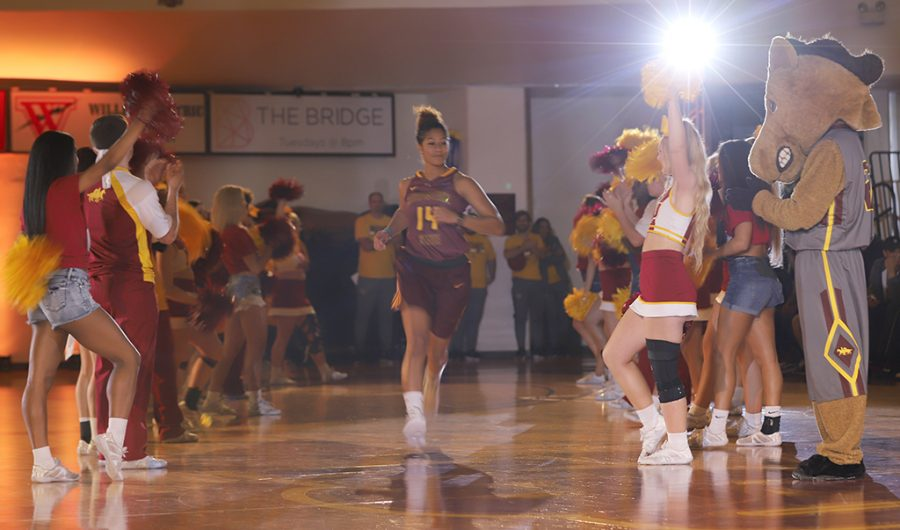 Cheerleaders and Maverick welcome Kityana Diaz, radiology sophmore, onto the court during Mustang Madness.