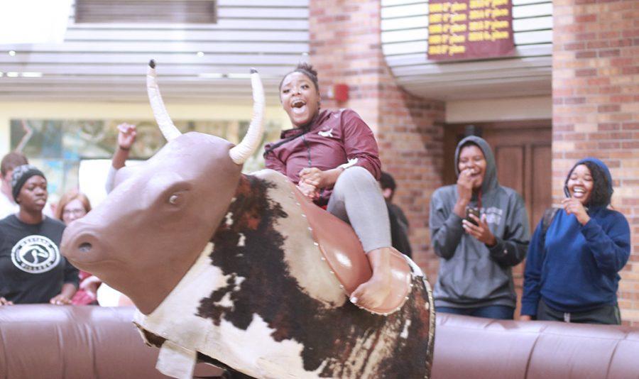 Giavonna Johnson, nursing freshman, falls off the bull at Mavericks 12th birthday party in CSC Comache Suites and Atrium Oct. 24.