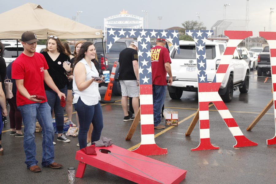 Tau Kappa Epsilon member Kyle Carpenter, junior mechanical engineering major, and Gamma Phi Beta member Rachel Roberts, junior dental hygiene major, play cornhole at the Tau Kappa Epsilon booth for the tailgate on Oct. 6 2018 at Memorial Stadium.  Photo by Jared Bruner