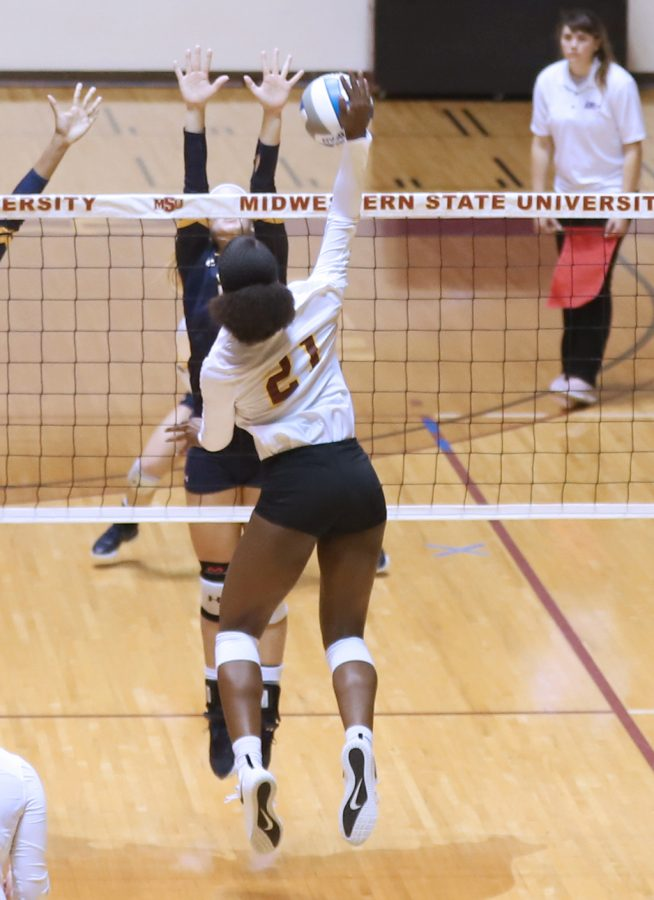 Raven Presley, engineering sophomore, attacks the set for a kill versus Texas A&M University- Commerce Oct. 9 in Ligon Coliseum. Photo by Kristin Silva