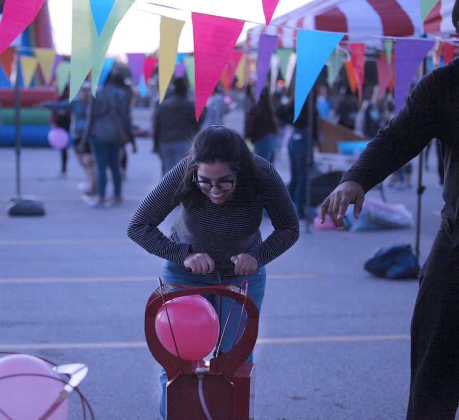 Jocelyn Diaz, history senior, pumps balloon in attempt to beat friends at a game at the MSU Texas Fair at Nocona Trail Oct.25.