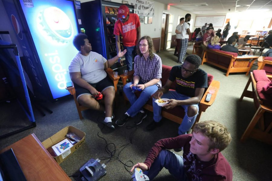 Nathan Snuggs, undecided freshmen, and David Hawkins, computer science freshman, play Donkey Kong Racing while other residence eat dinner at the Pierce Residence Hall Throwback Game night Sept. 29. Photo by Bradley Wilson