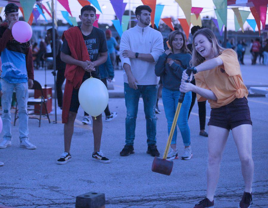 Kristin Silva, mass communication senior, attempts to pick up sledge hammer at MSU Texas Fair at Nocona Trail Oct.25.