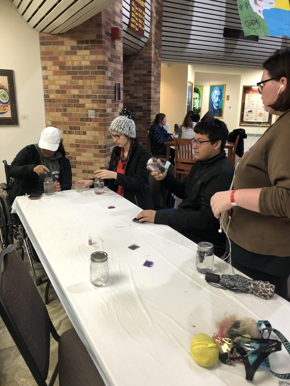 Dallas Wabbington, English sophomore,Kayleigh Stone, political science sophomore, Lorenzo Paredes, biology freshmen, Taylor Mash, chemistry sophomore sit at a table together while decorating their snow globes.