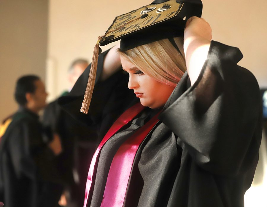 Marketing, Courtney Waldron fixes grauation cap before the ceremony on Dec. 15.