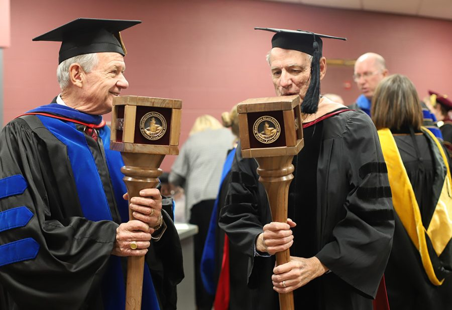 Harry Hewitt, professor of history, and Don Maxwell, professor of music, talk in the green room before graduation. As the two longest-serving faculty members, they carried maces and led the faculty at gradution.