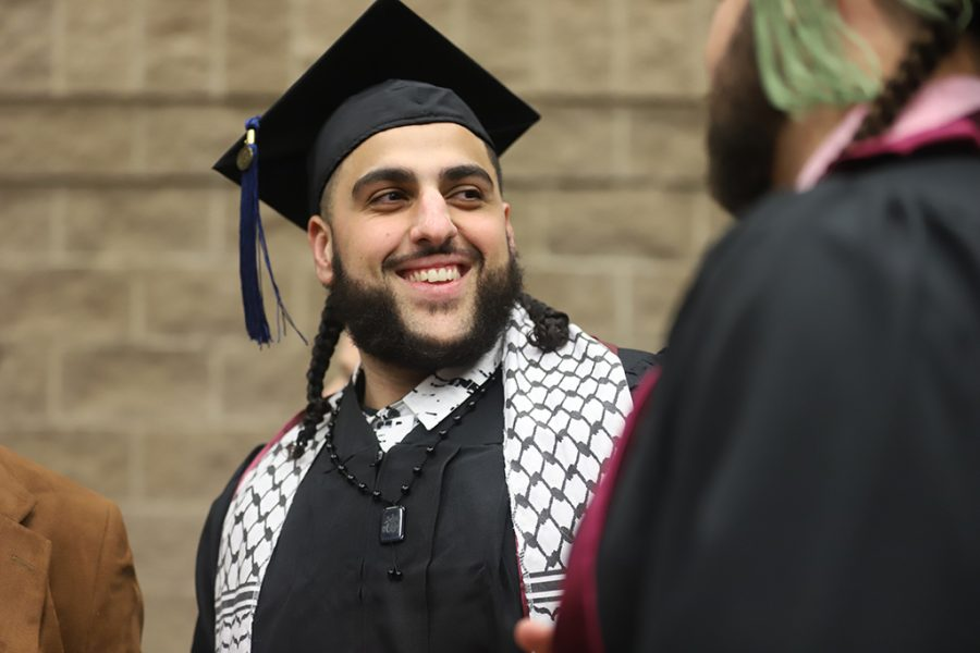 Islam Sbeigh, criminal justice, has a laugh with friends before preparing for the graduation ceremony on Dec. 15.